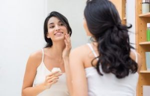 woman taking care of her skin in front of the mirror